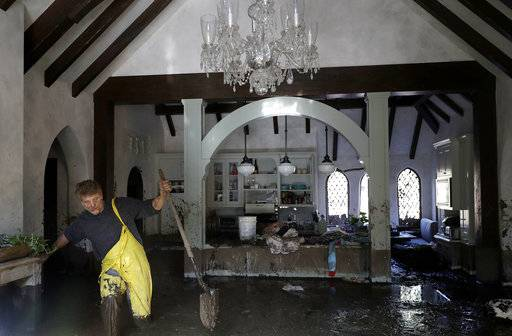 Bill Asher walks through mud in his home damaged by storms in Montecito, Calif., Thursday, Jan. 11, 2018. Rescue workers slogged through knee-deep ooze and used long poles to probe for bodies Thursday as the search dragged on for victims of the mudslides that slammed this wealthy coastal town.