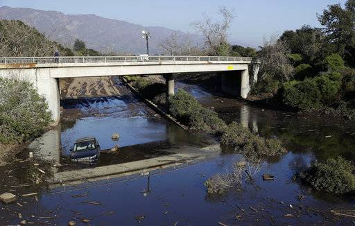 A car sits in flooded water on Highway 101 in Montecito, Calif., Thursday, Jan. 11, 2018. Rescue workers slogged through knee-deep ooze and used long poles to probe for bodies Thursday as the search dragged on for victims of Tuesday's storm after mudslides slammed this wealthy coastal town.