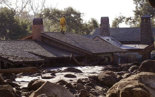 A Cal Fire search and rescue crew looks over a home damaged by storms in Montecito, Calif., Friday, Jan. 12, 2018.  The mudslide, touched off by heavy rain, took many homeowners by surprise early Tuesday, despite warnings issued days in advance that mudslides were possible because recent wildfires had stripped hillsides of vegetation that normally holds soil in place.