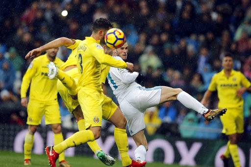 Real Madrid's Gareth Bale, centre and Villarreal's Alvaro Gonzalez go for a header in the goalmouth during a Spanish La Liga soccer match between Real Madrid and Villarreal at the Santiago Bernabeu stadium in Madrid, Spain, Saturday, Jan. 13, 2018.
