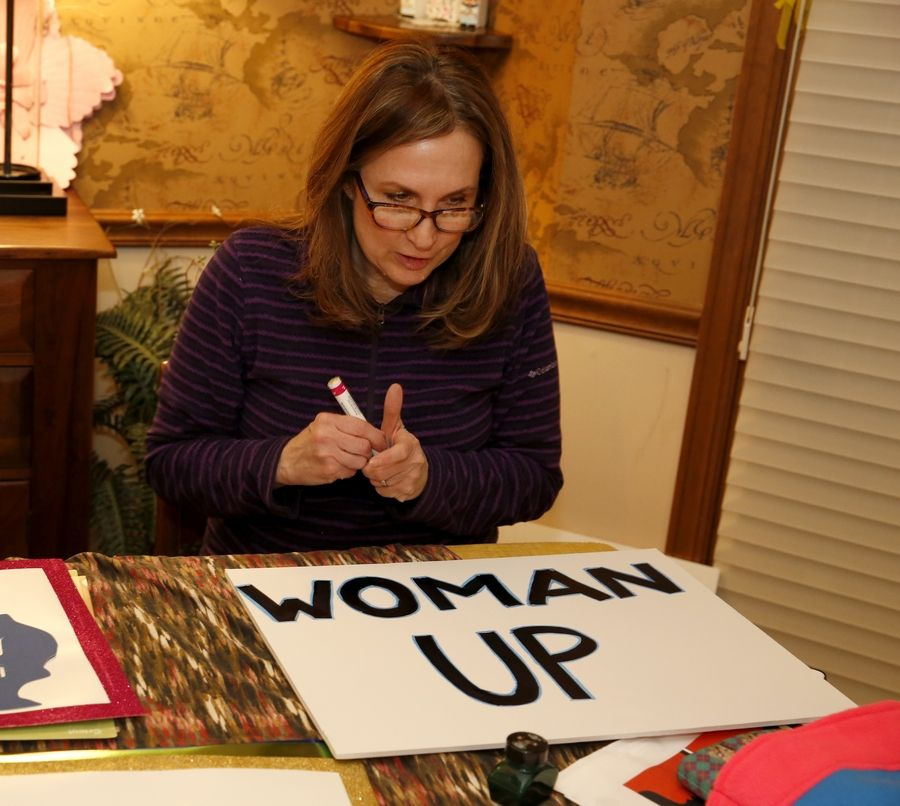 Lisa Rose, who lives in Naperville, works on a sign for the Saturday march in Chicago.
