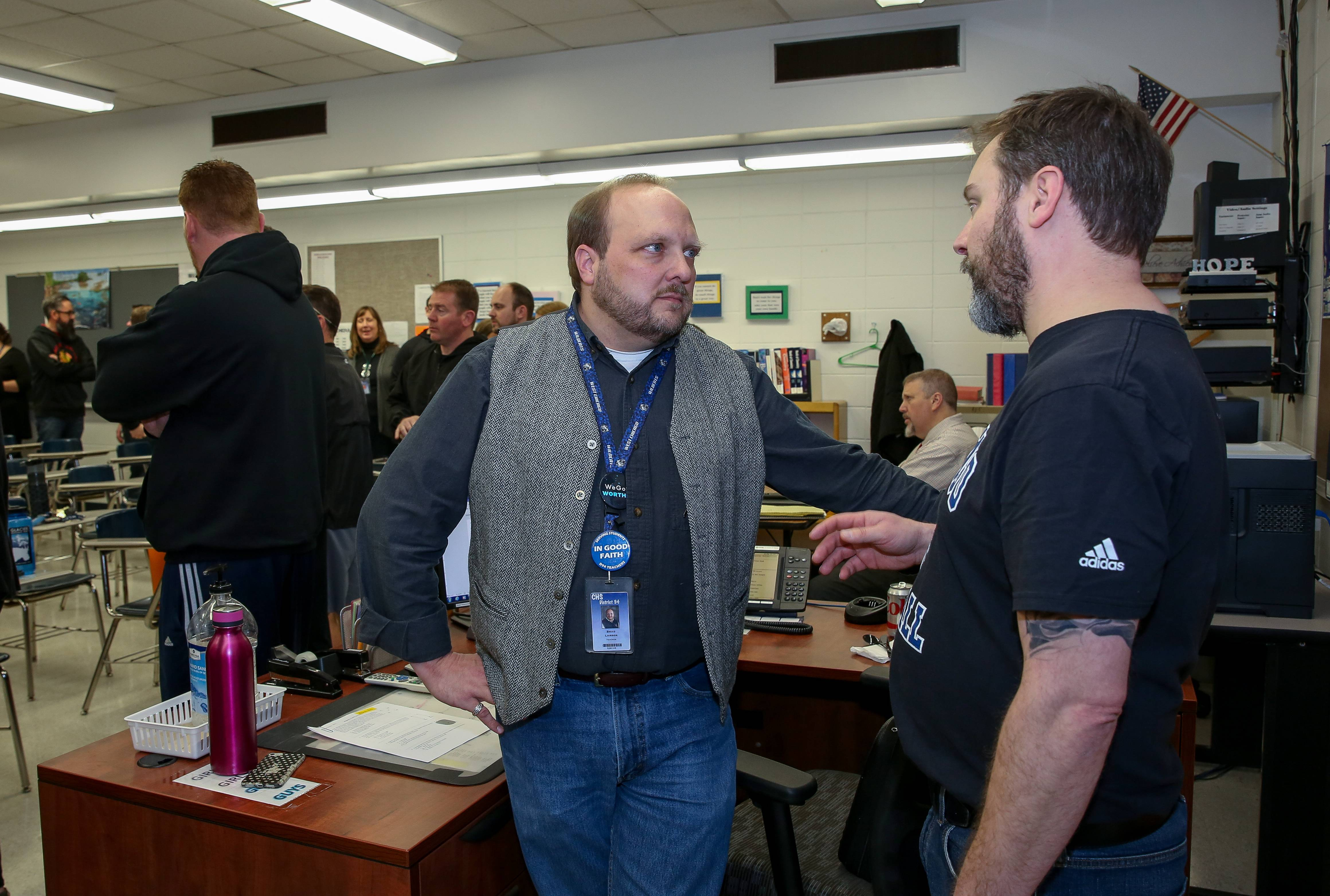 Brad Larson, left, president of West Chicago High School Teachers Association, speaks Friday with Nick Caltagirone, social studies teacher and a member of the union bargaining team, before voting to authorize a strike.