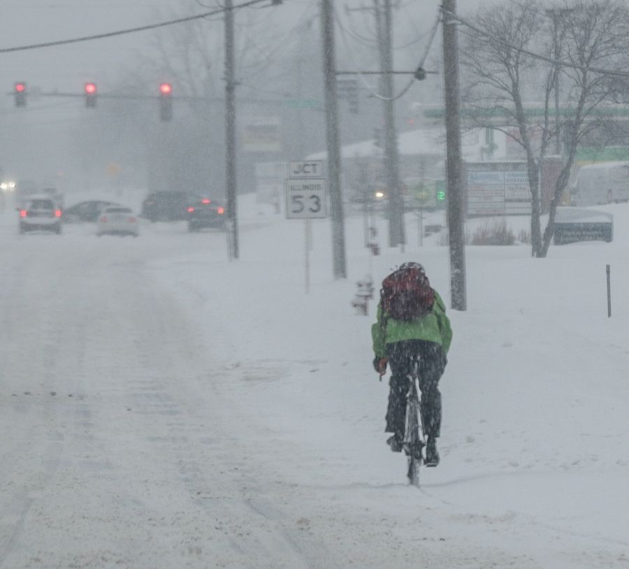 A bicyclist rides through the snow-covered streets in Itasca during Friday's snowfall.