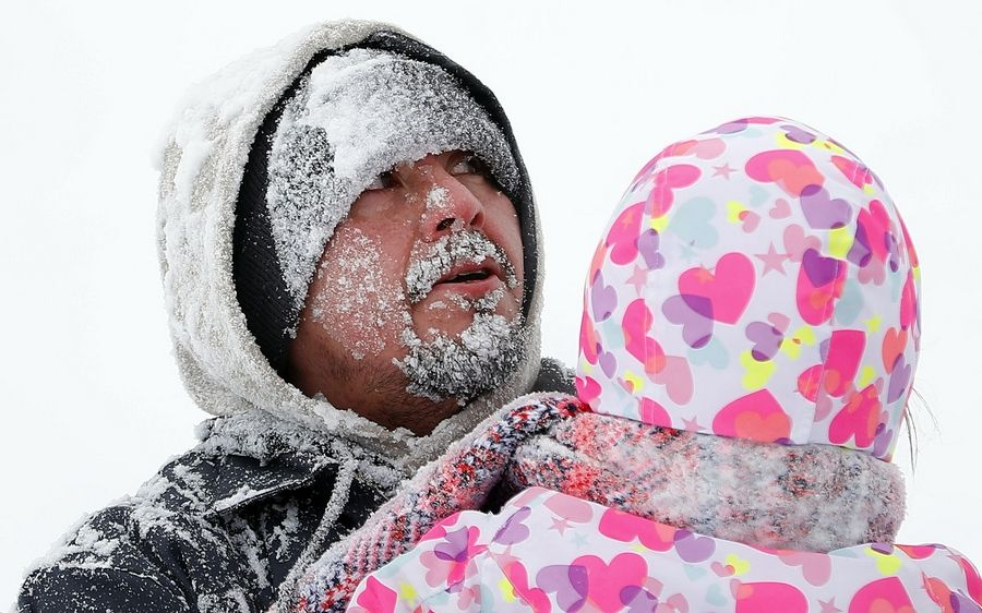 Christian Tenorio of Waukegan has a face full of snow after sledding with his 5-year-old niece Elly at Old School Forest Preserve in Libertyville after a winter storm dumped upward of 6 inches on the area Friday.