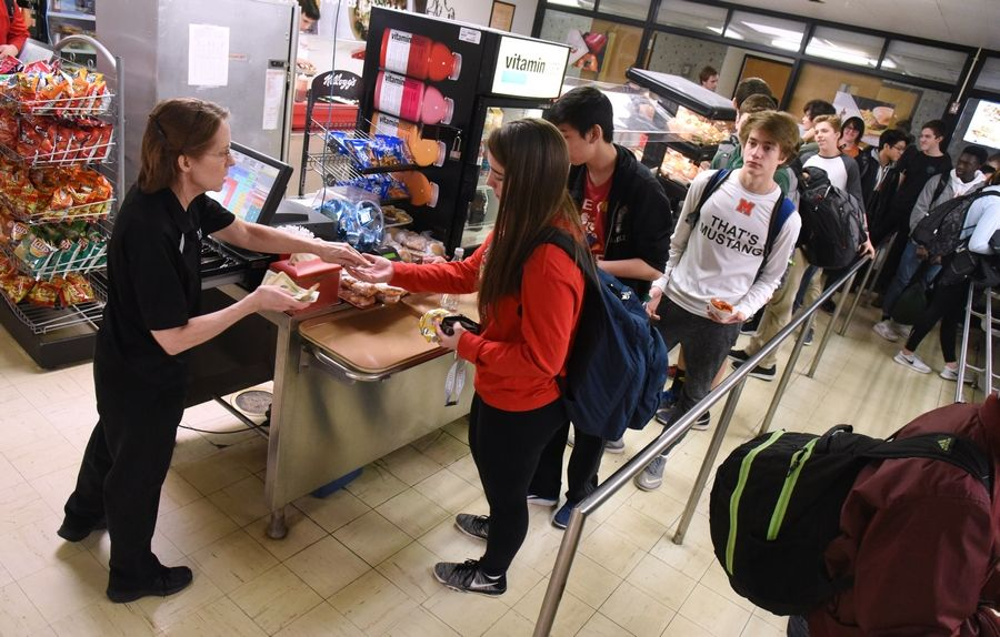 Mundelein High School students buy food Tuesday during one of the four lunch periods. The kitchen and cafeteria would be relocated as part of a facility improvement plan.