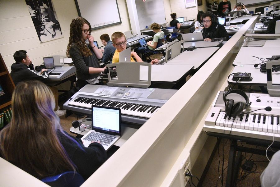 Stevenson High School assistant band director Maddie Vogler, standing, works with students Tuesday in the digital music lab. The lab will be turned into music space for breakout sessions this summer.
