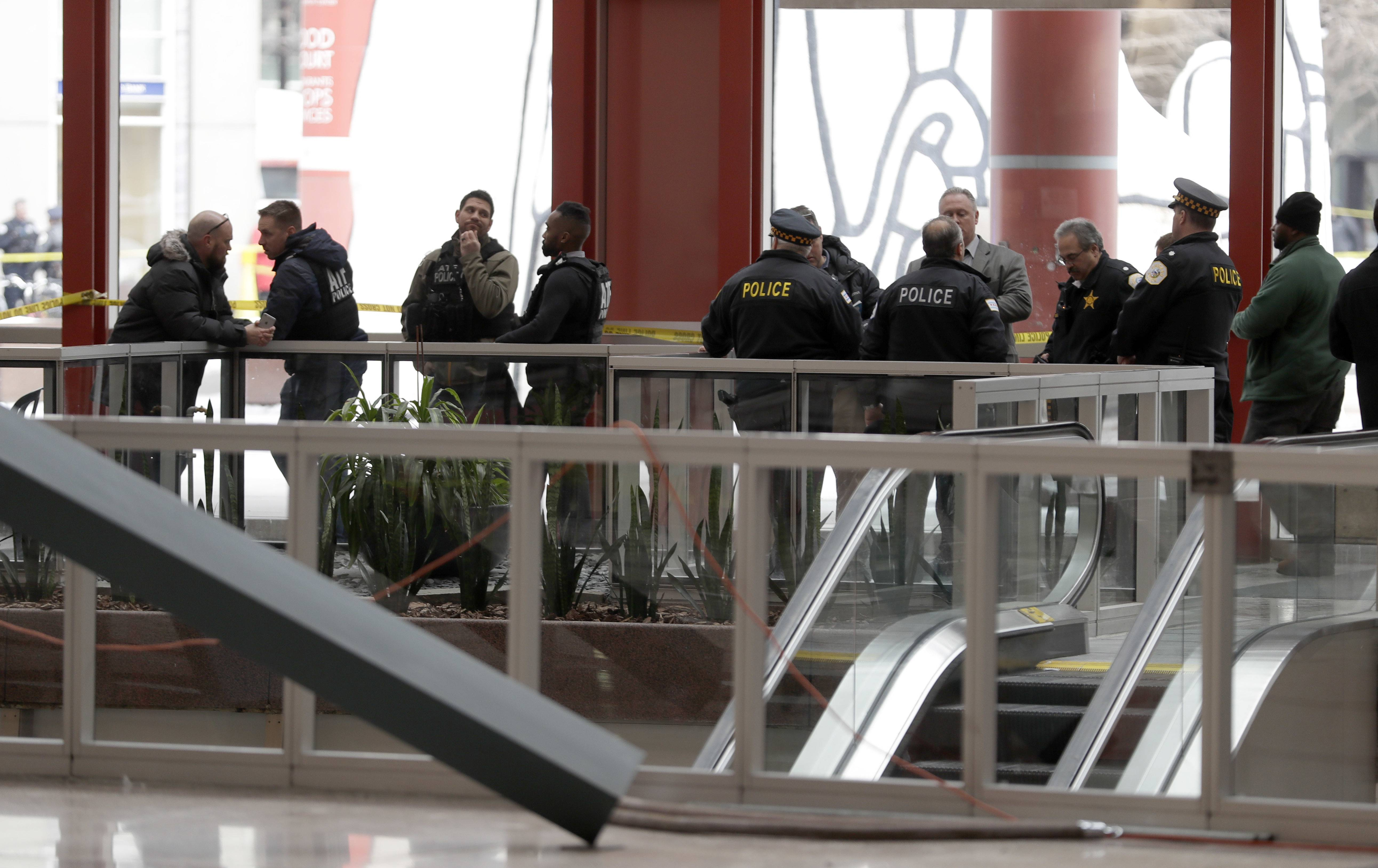 Chicago police officers remain on the scene inside the James R. Thompson Center after off-duty police Cmdr. Paul Bauer was shot several times as he went to assist tactical officers pursuing a fleeing suspect near the center on Tuesday in Chicago.