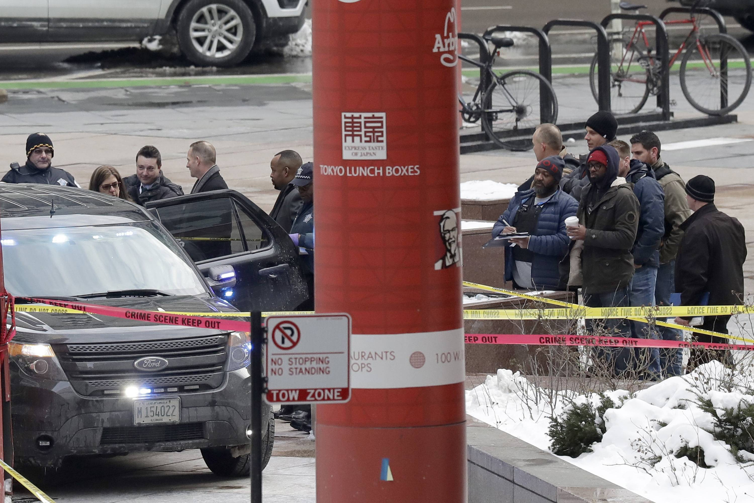 Chicago police officers remain on the scene outside the James R. Thompson Center after off-duty police Cmdr. Paul Bauer was shot several times as he went to assist tactical officers pursuing a fleeing suspect near the center on Tuesday in Chicago.