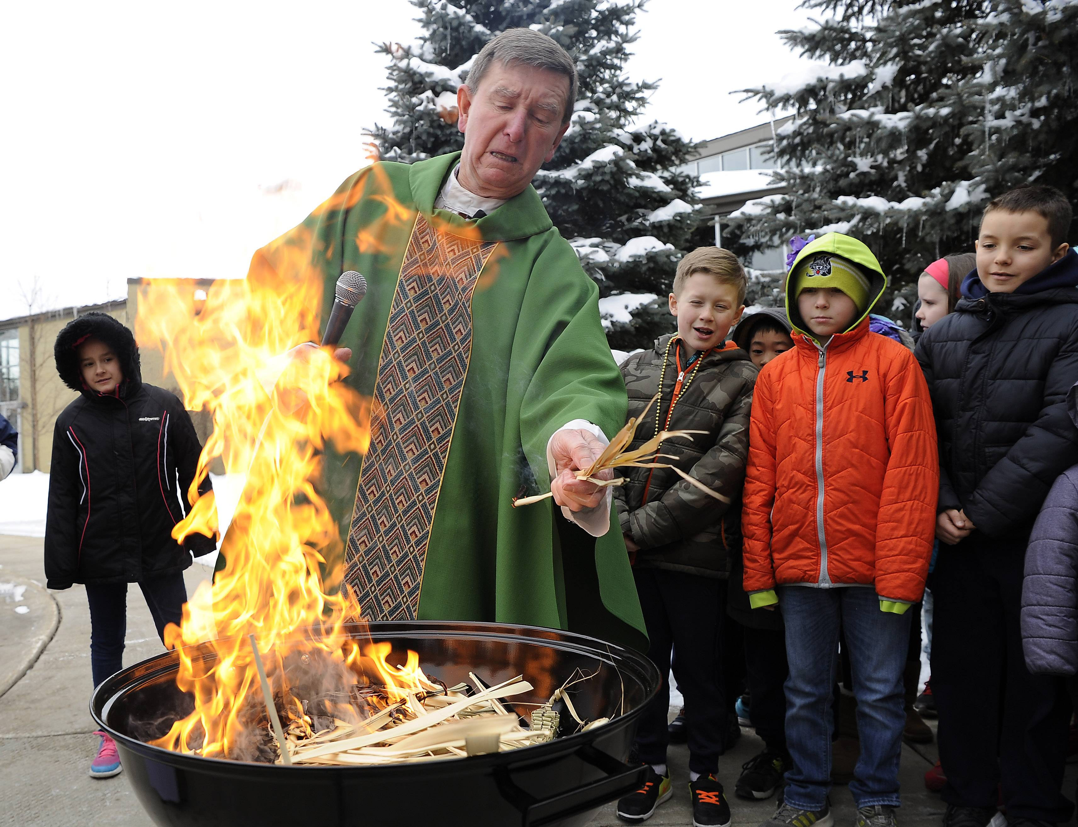The Rev. Curtis Lambert, pastor of St. Alphonsus Liguori Church in Prospect Heights, tosses palm leaves into a fire Tuesday as students from the parish school look on. The palms were burned to make ashes for Ash Wednesday services.