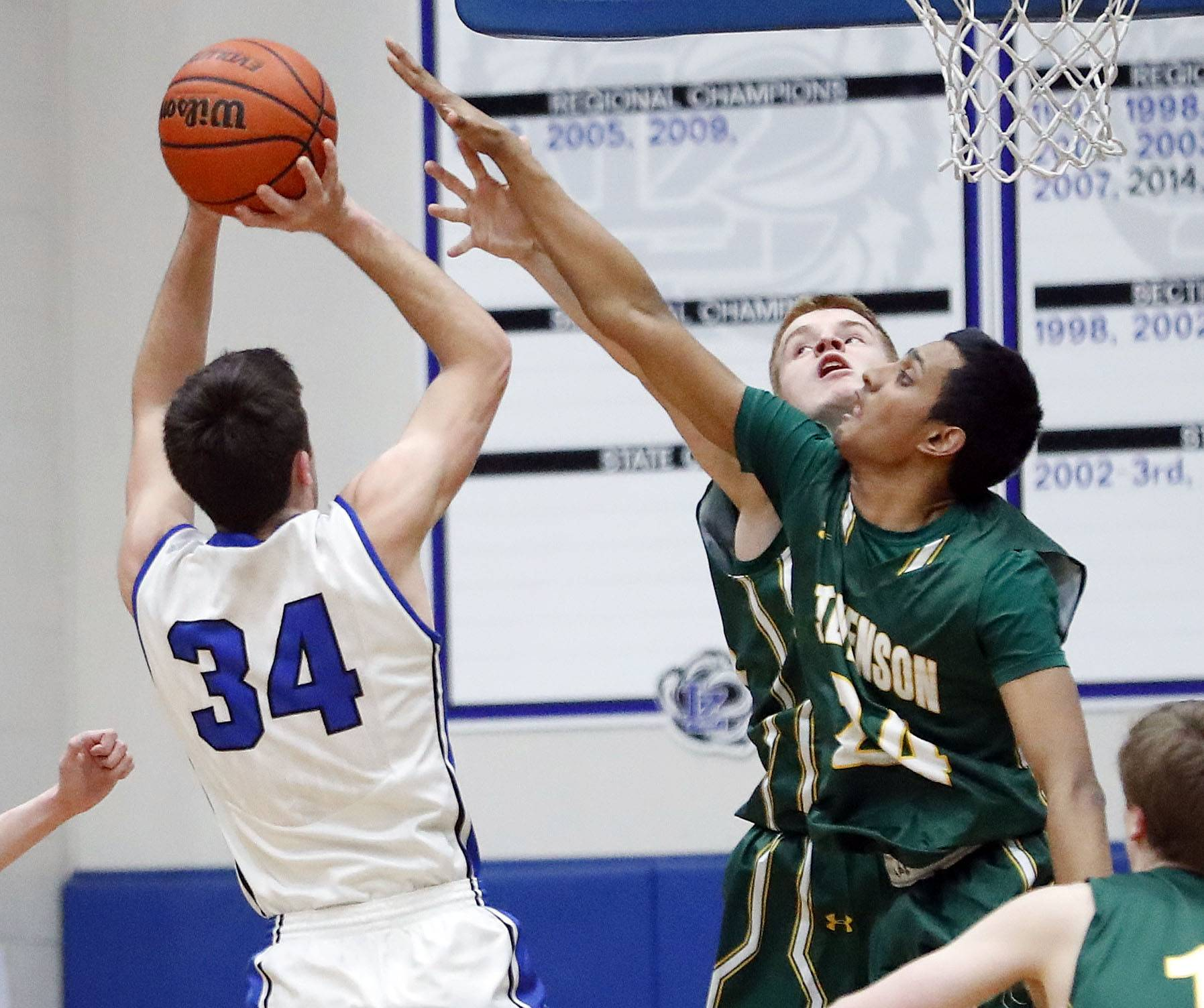 Lake Zurich's Ryan Kustor (34) shoots over Stevenson's Jackson Qualley and Samvit Ram on Tuesday night at Lake Zurich.