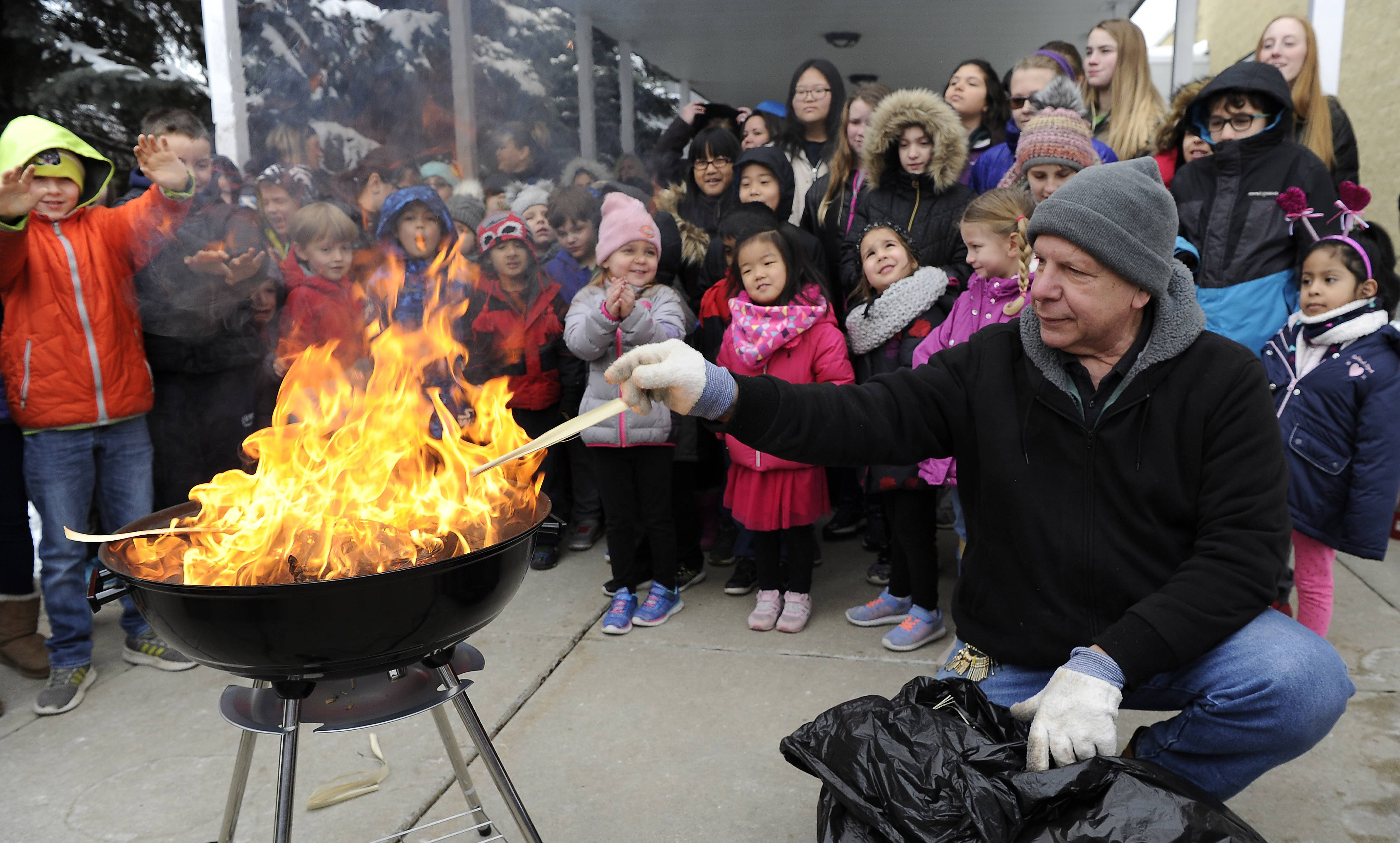 Rich Miceli, facility manager at St. Alphonsus Liguori Church in Prospect Heights, tosses palm leaves into a fire Tuesday as students from the parish school look on.