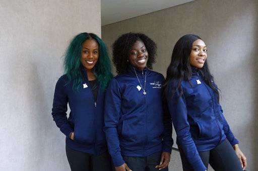 Members of the Nigerian women's bobsled team, from left, Akuoma Omeoga, Seun Adigun and Ngozi Onwumere, pose for a photograph during an interview with The Associated Press at the 2018 Winter Olympics in Pyeongchang, South Korea, Tuesday, Feb. 13, 2018. Despite being American born, Nigeria's first-ever bobsled team says they're representing the culture they were raised in.