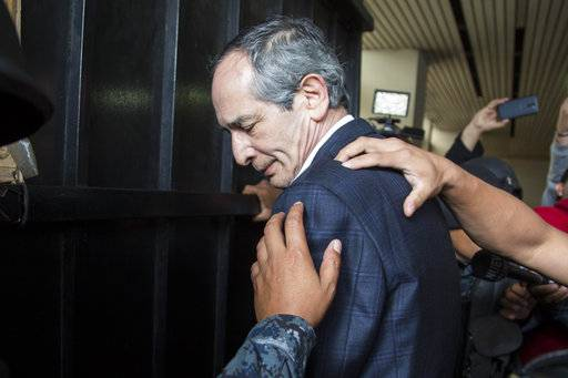 Police officers pat down former Guatemalan President Alvaro Colom before escorting him into a courthouse in Guatemala City, Tuesday, Feb. 13, 2018. Colom, who governed from 2008 to 2012, has been detained in a corruption case according to special prosecutor Juan Francisco Sandoval. (AP Photo/Luis Soto)