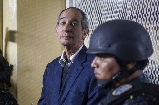 Former Guatemalan President Alvaro Colom is flanked by police as they wait to enter a holding cell in a courthouse, in Guatemala City, Tuesday, Feb. 13, 2018. Colom, who governed from 2008 to 2012, has been detained in a corruption case according to special prosecutor Juan Francisco Sandoval.