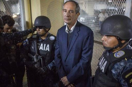 Former Guatemalan President Alvaro Colom is flanked by police in a courtroom in Guatemala City, Tuesday, Feb. 13, 2018. Colom, who governed from 2008 to 2012, has been detained in a corruption case according to special prosecutor Juan Francisco Sandoval.