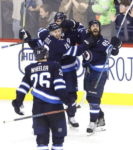 Winnipeg Jets' Blake Wheeler (26), Bryan Little (18), Mark Scheifele (55) and Mathieu Perreault (85) celebrate after Scheifele scored against the Washington Capitals with 15 seconds left during the third period of an NHL hockey game Tuesday, Feb. 13, 2018, in Winnipeg, Manitoba. (Trevor Hagan/The Canadian Press via AP)