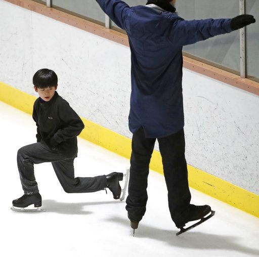 Keita Horiko, left, the 10-year-old U.S. Figure Skating juvenile boys champion, watches his coach, Kevin Coppola, during a training session Thursday, Feb. 8, 2018, at the Ice House in Hackensack, N.J. Asian-Americans are taking center ice during the figure skating competition at the Pyeongchang Olympics, where half of the U.S. figure skating team is Asian-American.