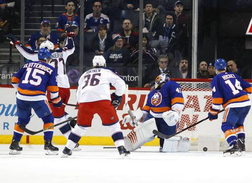 Columbus Blue Jackets right wing Josh Anderson (77) celebrate as New York Islanders goaltender Jaroslav Halak (41) of Slovakia looks at the puck in the goal behind him after Columbus Blue Jackets center Pierre-Luc Dubois (not shown) scored during the second period of an NHL hockey game in New York, Tuesday, Feb. 13, 2018. (AP Photo/Kathy Willens)