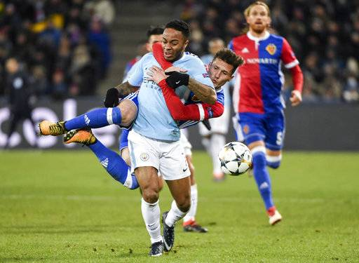 Basel's Taulant Xhaka, behind, clings to Manchester City's Raheem Sterling, front, and gets a yellow card for this action, during the UEFA Champions League round of sixteen first leg soccer match between Switzerland's FC Basel 1893 and England's Manchester City, in the St. Jakob-Park stadium in Basel, Switzerland, on Tuesday, Feb. 13, 2018. (Georgios Kefalas/Keystone via AP)