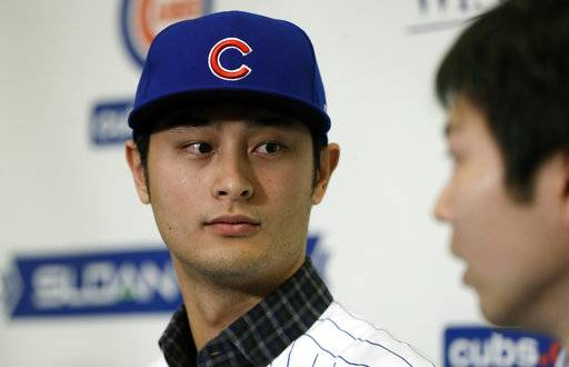 Chicago Cubs starting pitcher Yu Darvish looks towards interpreter Daichi Sekizaki during a media availability at the team's spring training baseball facility Tuesday, Feb. 13, 2018, in Mesa, Ariz. Darvish signed a $126 million, six-year contract over the weekend.
