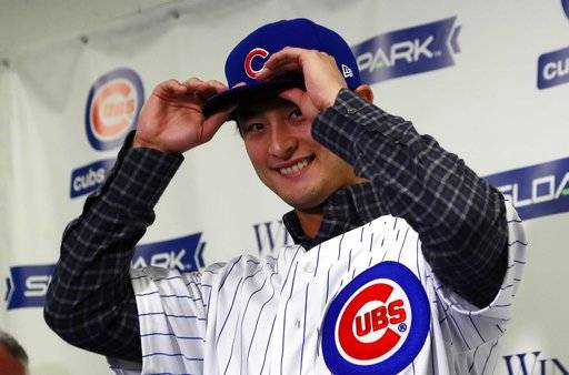 Chicago Cubs starting pitcher Yu Darvish tries on the team's cap during a media availability at the team's spring training baseball facility Tuesday, Feb. 13, 2018, in Mesa, Ariz. Darvish signed a $126 million, six-year contract over the weekend.