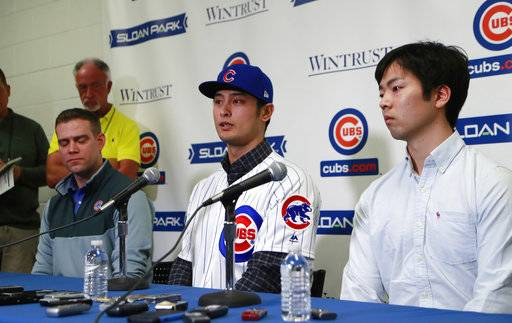 Chicago Cubs starting pitcher Yu Darvish responds during a media availability at the team's spring training baseball facility Tuesday, Feb. 13, 2018, in Mesa, Ariz. Darvish signed a $126 million, six-year contract over the weekend. At left is team President of Baseball Operations Theo Epstein and interpreter Daichi Sekizaki at right.