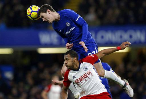 Chelsea's Andreas Christensen, top, heads the ball clear under pressure from West Bromwich Albion's Salomon Rondon during the English Premier League soccer match between Chelsea and West Bromwich Albion at Stamford Bridge stadium in London, Monday, Feb. 12, 2018. (AP Photo/Alastair Grant)