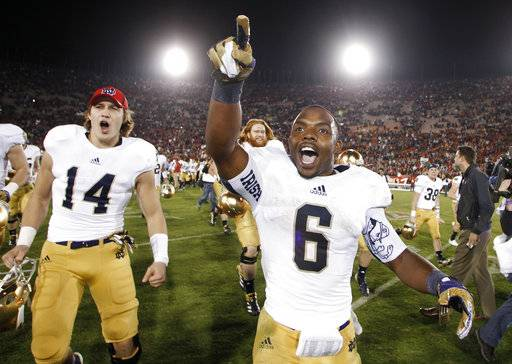 FILE - In this Nov. 24, 2012, file photo, Notre Dame running back Theo Riddick, right, and wide receiver Luke Massa, left, celebrate after Notre Dame defeated Southern California 22-13 in an NCAA college football game in Los Angeles. The NCAA has denied Notre Dame's appeal of a decision to vacate 21 victories because of academic misconduct, including all 12 wins from the school's 2012 national championship game run. (AP Photo/Danny Moloshok, File)