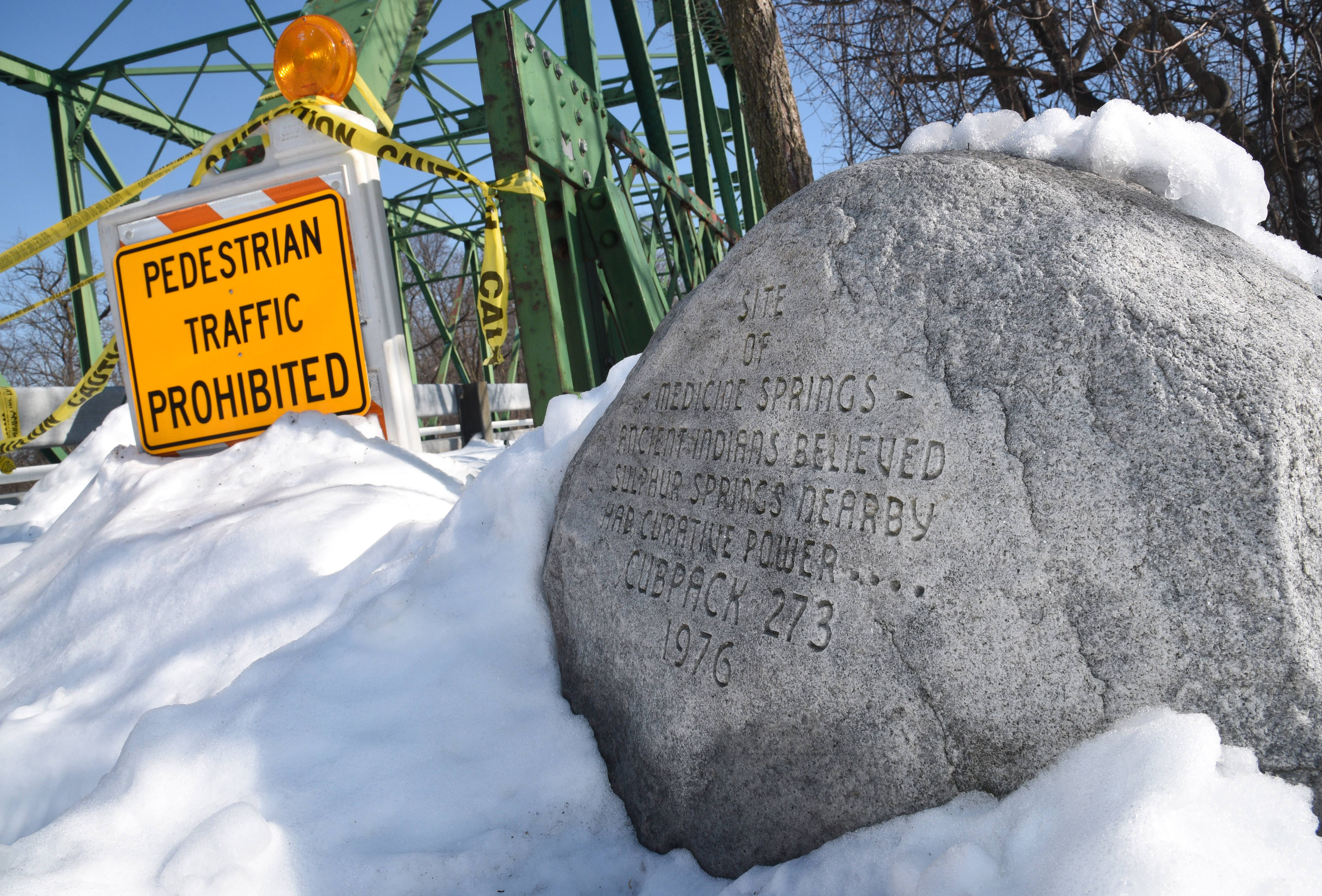 A boulder on the west side of the Rockland Road bridge over the Des Plaines River will be protected when the decorative steel truss is removed. It has an inscription from a 1976 Cub Scout project.