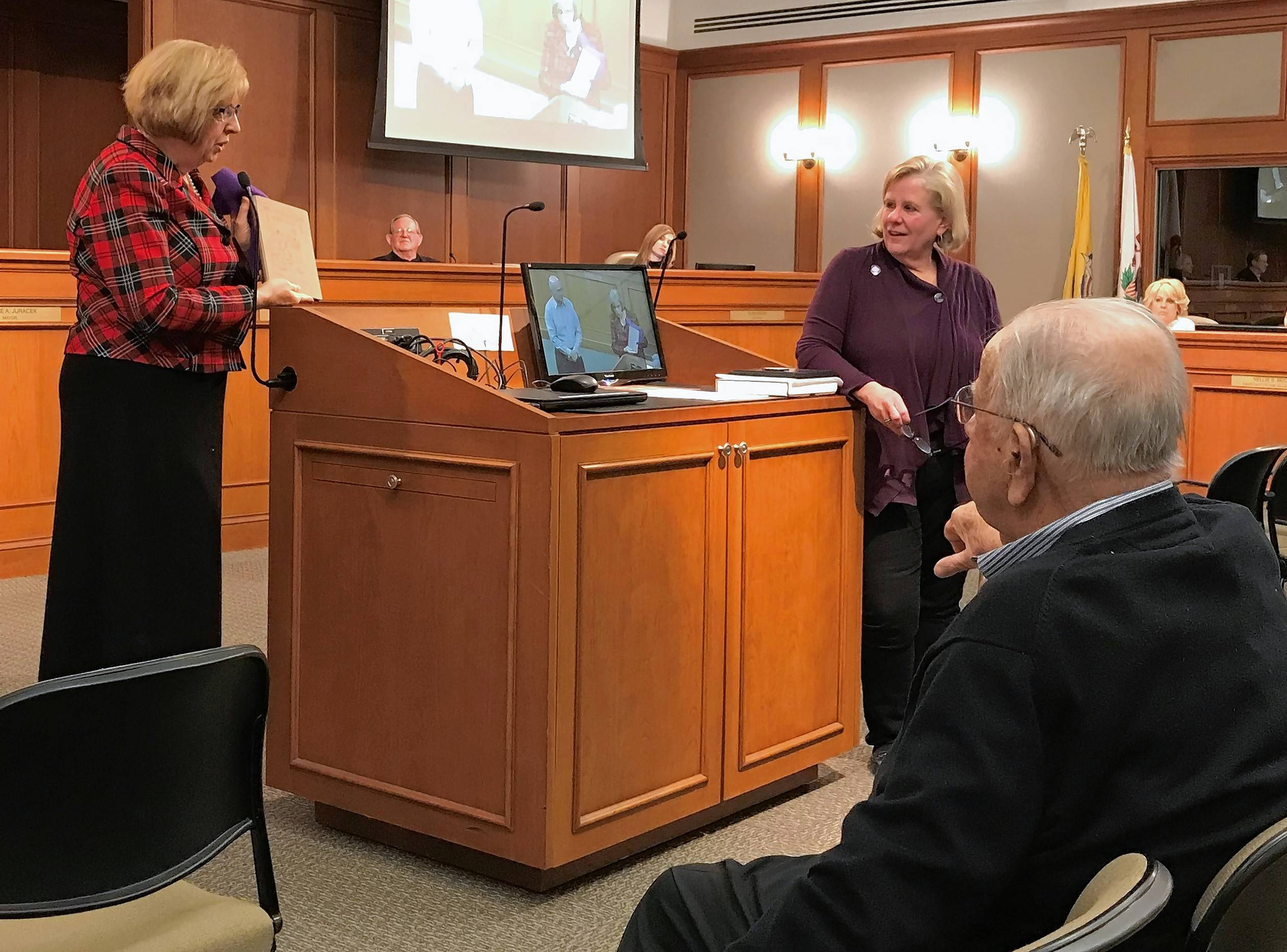 Jean Murphy, right, who co-chaired Mount Prospect's 100-year celebration with former Trustee Leo Floros, seated, were honored with others by Mayor Arlene Juracek, left, at last week's village board meeting.