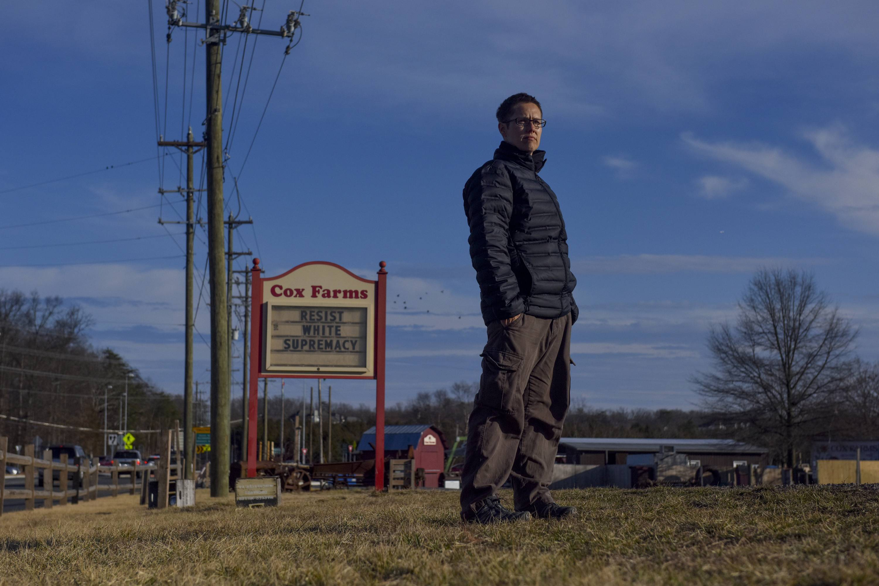Aaron Cox-Leow stands on her family's farm in Centreville, Virginia, near the sign that has caused a furor on social media.