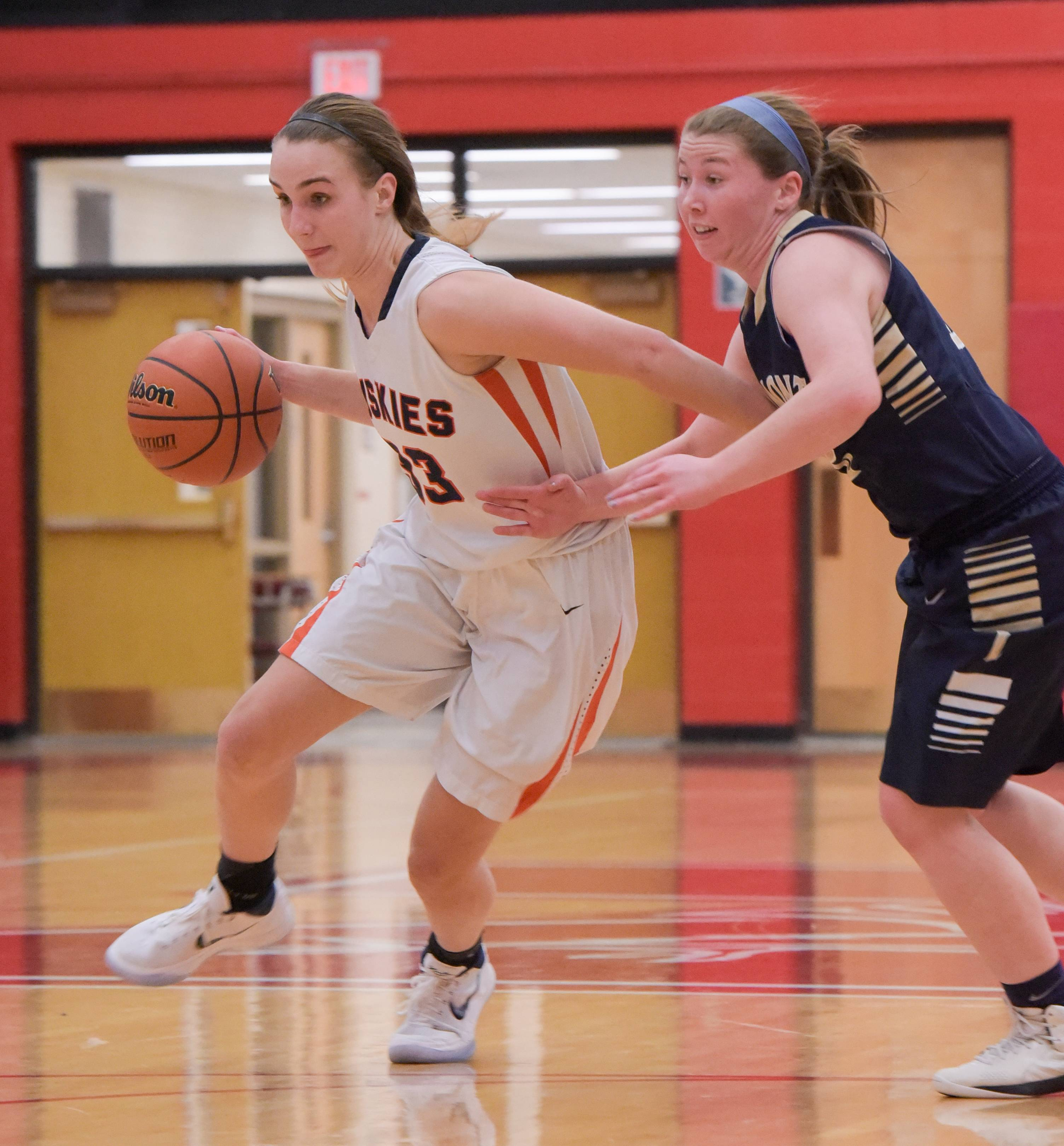 Naperville North's Greta Kampshroeder (33) drives around Lemont's Michelle Jerantowski (12)during the Class 4A girls basketball regional semifinals on February 14, 2018.
