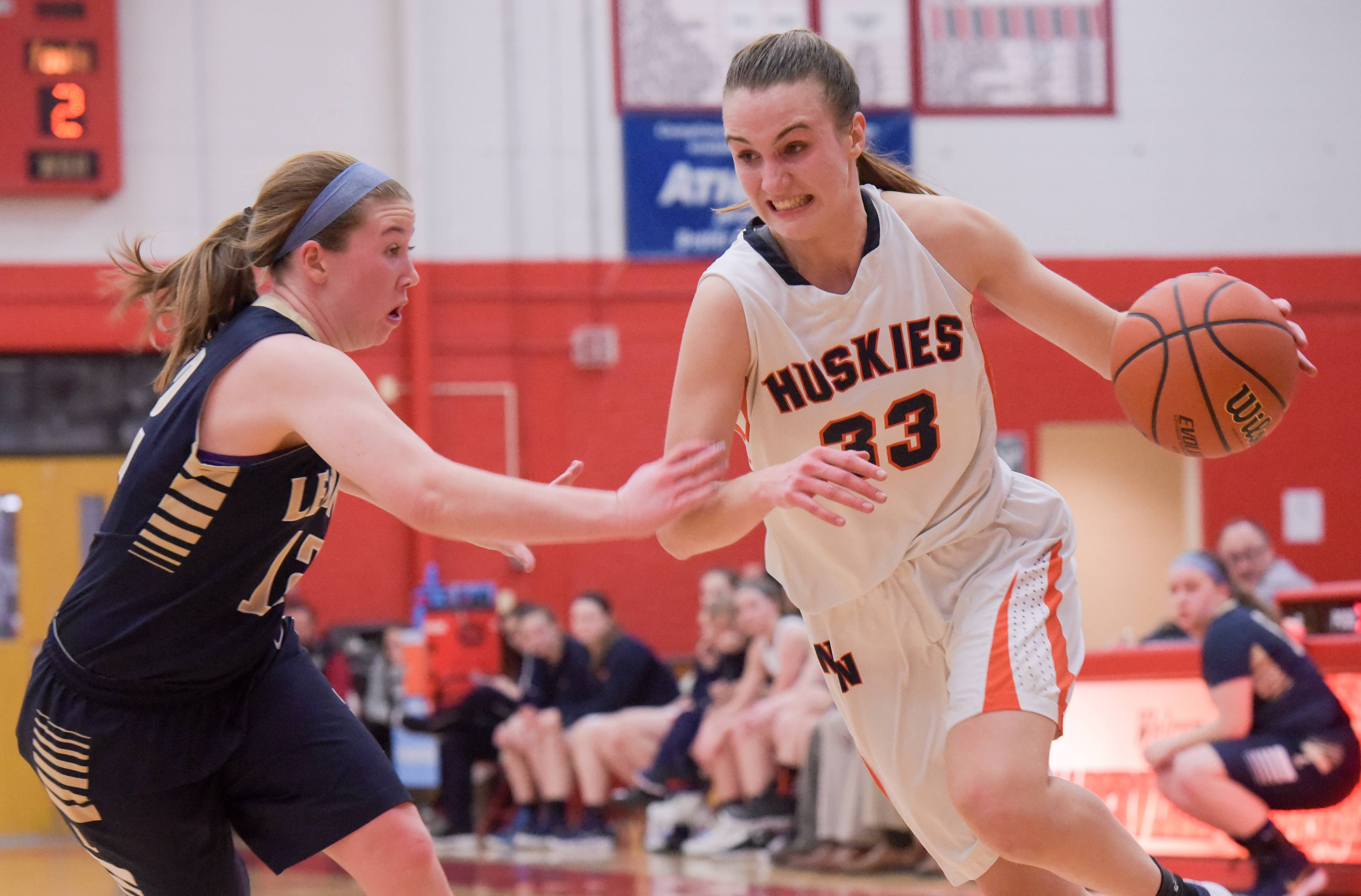 Naperville North's Greta Kampshroeder (33) drives around Lemont's Michelle Jerantowski (12) during the Class 4A girls basketball regional semifinals on February 14, 2018.