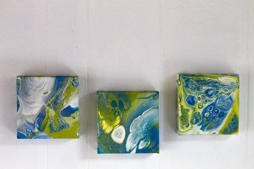 This Feb. 11, 2018 photo shows the results of using three different mediums used to paint and make art on canvas_ Elmer's glue, Floetrol paint additive and Liquitex pouring medium, in Hopkinton, N.H. When it comes to pour painting, not only are there many techniques for applying the paint _ puddle pour, dirty pour, flip cup, swipe _ but also many recipes for producing a fluid mixture that will glide smoothly across the canvas. (AP Photo/Holly Ramer)