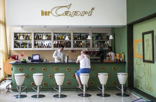 "FILE - In this Sept. 12, 2017, file photo, a customer sits at the lobby bar of the Hotel Capri in Havana, Cuba. Doctors are releasing the first detailed medical reports about the hearing, vision, balance and brain symptoms suffered in what the State Department has called ""health attacks� on U.S. diplomats in Cuba. Still missing: A clear diagnosis of just what happened to trigger their mysterious health problems. (AP Photo/Desmond Boylan)"