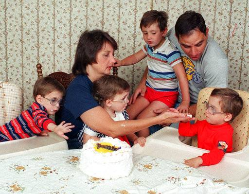 FILE - In this May 21, 1988 file photo, the three surviving Frustaci septuplets, Stephen, Patricia, and Richard, seated from left, join parents Patti and Sam Frustaci and older brother Joseph, 4, as they dig into cake to celebrate their third birthday in Riverside, Calif. Patricia Frustaci, a Southern California woman who made national headlines in 1985 when she gave birth to seven children, has died at age 63. Her eldest son, Joseph Frustaci, says his mother died Saturday, Feb. 10, 2018, in San Diego. She had suffered from pulmonary fibrosis. (AP Photo/Douglas C. Pizac, File)