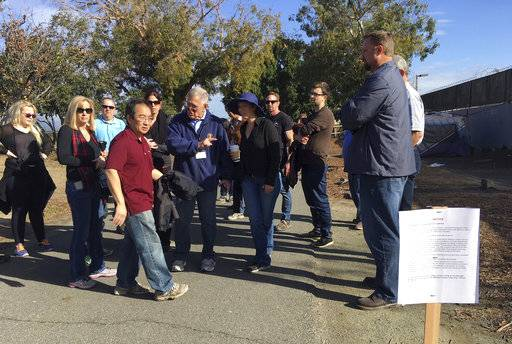 Judge David Carter, a U.S. District Judge, sixth from left, pointing, followed by an entourage of three dozen lawyers, Orange County workers, nonprofit staff and local officials tours a Southern California homeless encampment amid a lawsuit over efforts by local officials to shut it down in Santa Ana, Calif., Wednesday, Feb. 14, 2018. Judge Carter is overseeing a lawsuit filed by homeless advocates over the planned closure of the encampment on the county-owned trail. (AP Photo/Amy Taxin)
