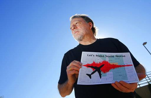 FILE - In this Feb. 6, 2015 file photo, Steve Dreiseszun, a resident of the F.Q. Story historic district in Phoenix, holds a graphic of the increased noise brought on by airplanes flying along new flight paths out of Phoenix Sky Harbor International Airport. More than three years after waking up to find window-rattling flights rerouted over their homes in an airborne highway, residents of Phoenix's historic downtown districts said they finally felt the FAA was listening to them. (AP Photo/Ross D. Franklin, File)