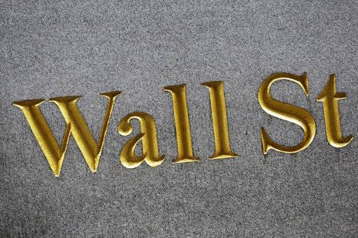 FILE - This July 6, 2015, file photo shows a sign for Wall Street carved into the side of a building in New York. The U.S. stock market opens at 9:30 a.m. EST on Wednesday, Feb. 14, 2018. (AP Photo/Mark Lennihan, File)