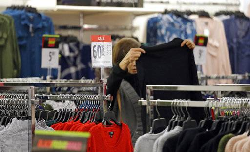 FILE- In this Nov. 24, 2017, file photo, a shopper looks over clothing at a J.C. Penney store in Seattle. On Wednesday, Feb. 14, 2018, the Labor Department reports on U.S. consumer prices for January. (AP Photo/Elaine Thompson, File)
