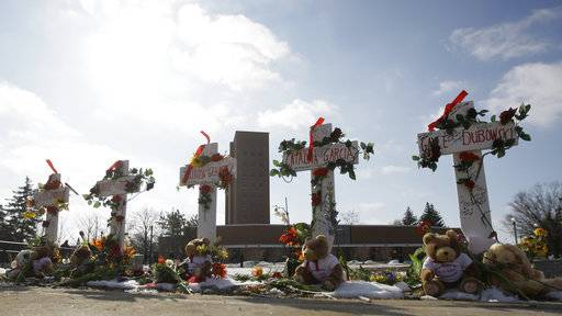 FILE - In this Feb. 14, 2009 file photo, Five crosses stand outside Northern Illinois University's Cole Hall marking the one year anniversary of a shooting in the NIU lecture hall that left five students dead in DeKalb, Ill. NIU will mark the tenth anniversary of the shooting with a memorial service Wednesday, Feb. 14, 2018. Bells will toll and wreaths will be placed at a memorial at 3:06 p.m. at the school's DeKalb campus. School officials say the university community will observe a moment of reflection. (AP Photo/M. Spencer Green, File)