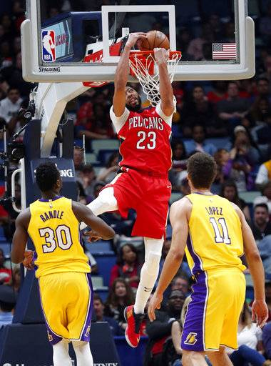 New Orleans Pelicans forward Anthony Davis (23) dunks as Los Angeles Lakers forward Julius Randle (30) and center Brook Lopez (11) watch during the first half of an NBA basketball game in New Orleans, Wednesday, Feb. 14, 2018. (AP Photo/Gerald Herbert)