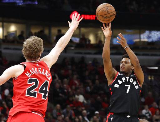 Toronto Raptors guard Kyle Lowry, right, shoots against Chicago Bulls forward Lauri Markkanen during the first half of an NBA basketball game Wednesday, Feb. 14, 2018, in Chicago. (AP Photo/Nam Y. Huh)