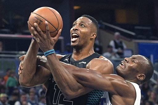 Charlotte Hornets center Dwight Howard (12) is fouled by Orlando Magic center Bismack Biyombo, right, while going up for a shot during the first half of an NBA basketball game Wednesday, Feb. 14, 2018, in Orlando, Fla. (AP Photo/Phelan M. Ebenhack)