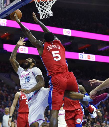 Miami Heat's James Johnson (16) takes a shot as Philadelphia 76ers' Amir Johnson (5) defends in the first half of an NBA basketball game, Wednesday, Feb. 14, 2018, in Philadelphia. (AP Photo/Michael Perez)