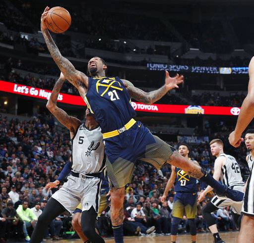 Denver Nuggets forward Wilson Chandler, front, reaches over San Antonio Spurs guard Dejounte Murray for the ball during the first half of an NBA basketball game Tuesday, Feb. 13, 2018, in Denver.