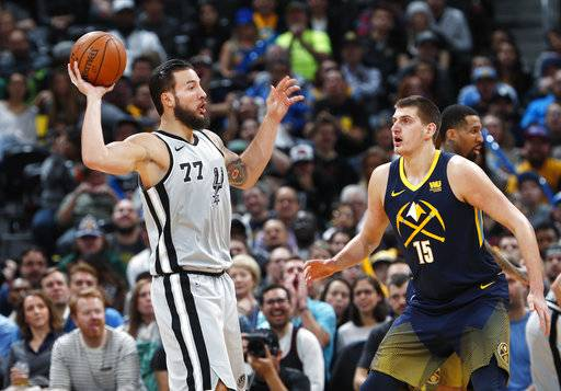 San Antonio Spurs center Joffrey Lauvergne, left, looks to pass the ball as Denver Nuggets center Nikola Jokic defends during the first half of an NBA basketball game Tuesday, Feb. 13, 2018, in Denver.