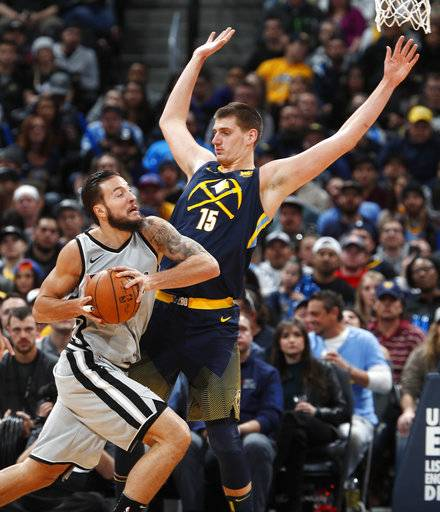San Antonio Spurs center Joffrey Lauvergne, left, drives against Denver Nuggets center Nikola Jokic on the way to to the basket during the first half of an NBA basketball game Tuesday, Feb. 13, 2018, in Denver.