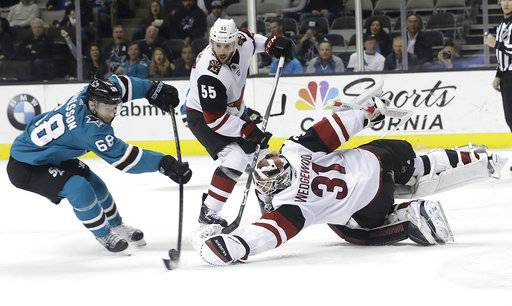 Arizona Coyotes goaltender Scott Wedgewood (31) reaches for the puck in front of San Jose Sharks right wing Melker Karlsson (68), from Sweden, during the second period of an NHL hockey game in San Jose, Calif., Tuesday, Feb. 13, 2018.