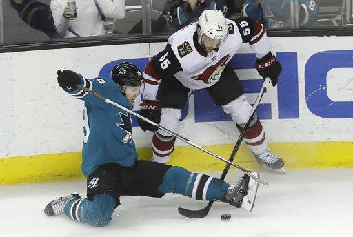 San Jose Sharks center Logan Couture, bottom, falls in front of Arizona Coyotes defenseman Jason Demers (55) during the third period of an NHL hockey game in San Jose, Calif., Tuesday, Feb. 13, 2018.
